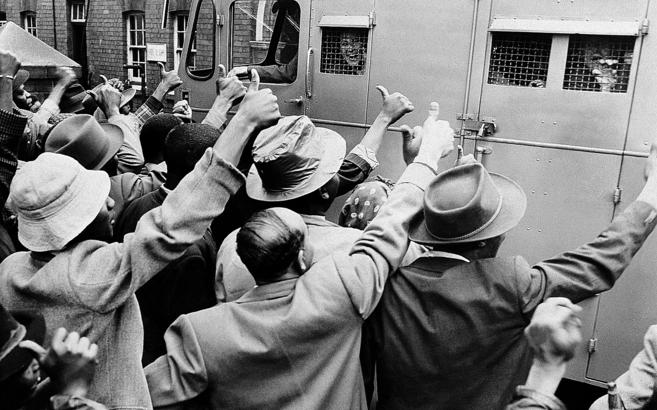 Partidarios del CNA saludan al camión en el que viajaba Mandela camino al tribunal de Johannesburgo. REUTERS